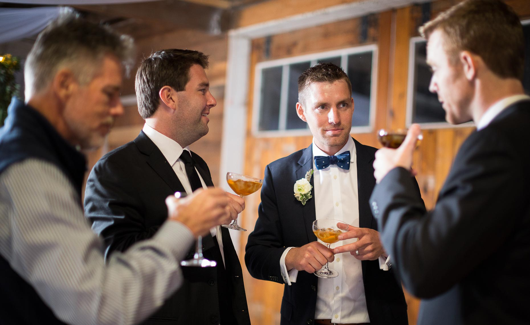 Groomsmen gather in barn during vintage style whistler wedding