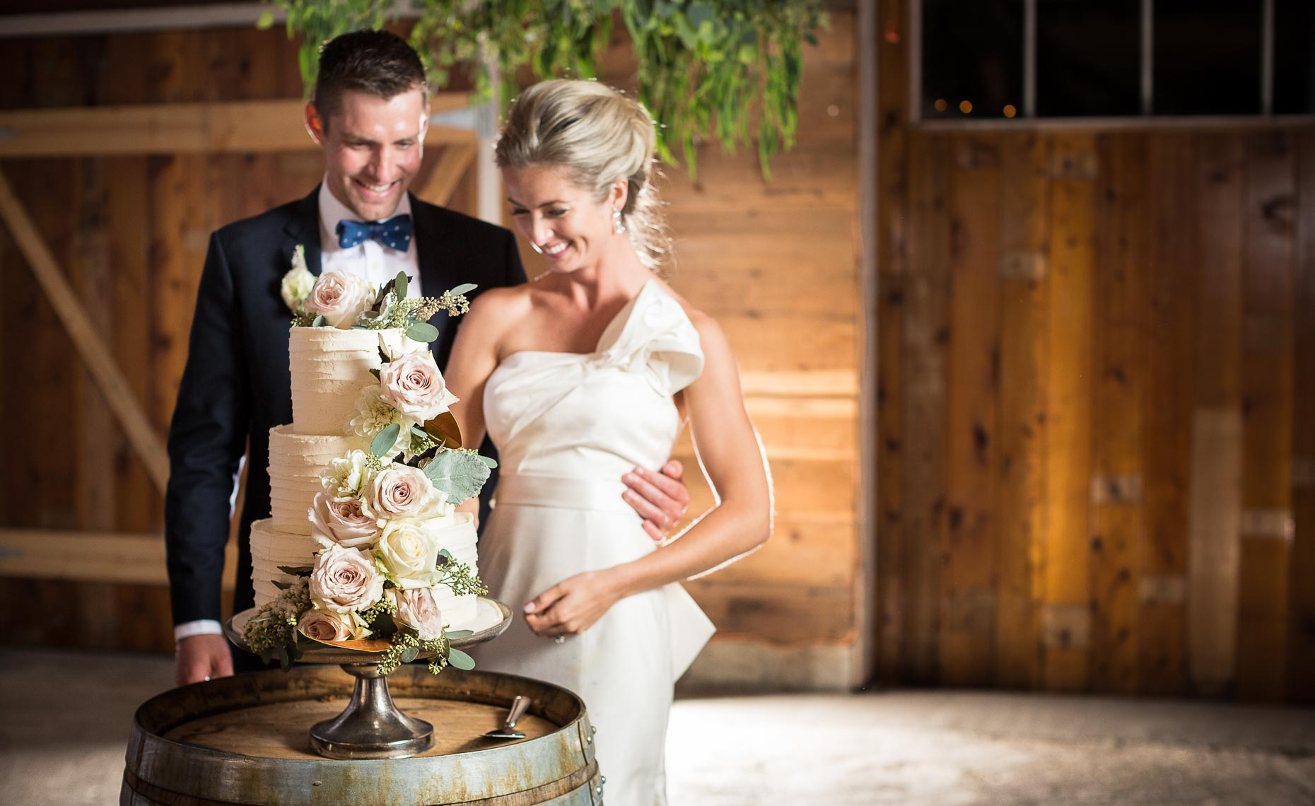 Elegant wedding couple in whistler cut the cake in a vintage barn