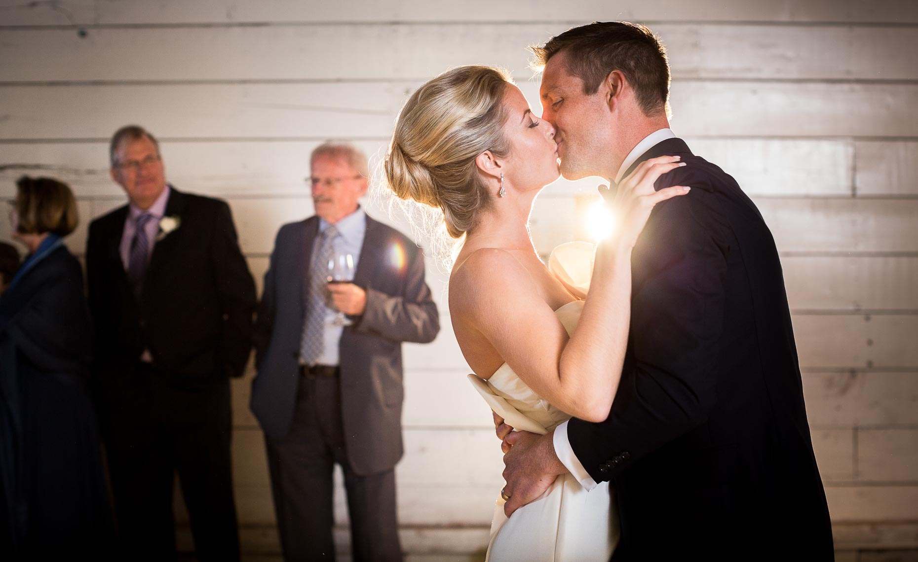 Bride and groom kiss after first dance in Pemberton vintage barn wedding.