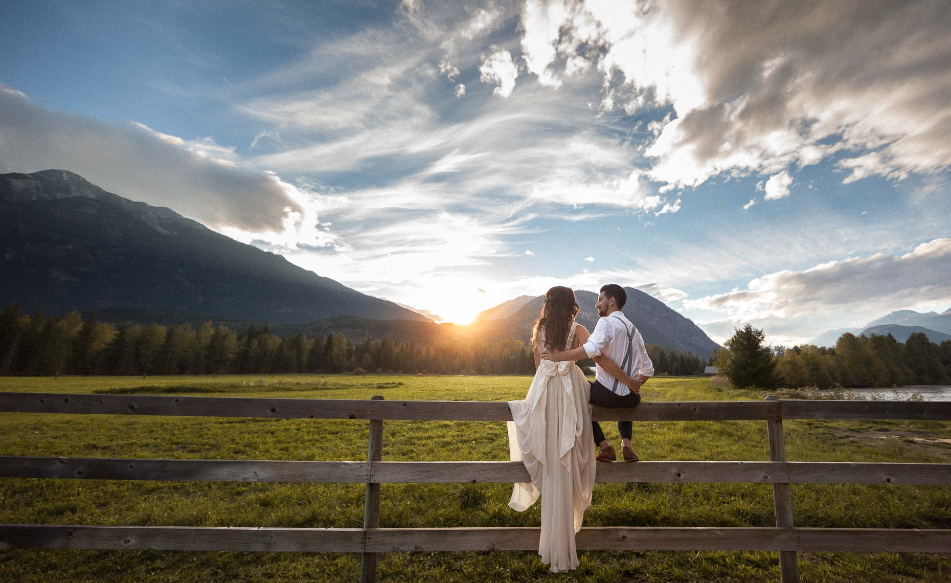 Bride and groom sitting on a fence at sunset farm wedding in Pemberton BC near Whistler.